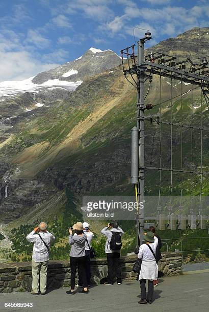 StartBahnhof Pontresina Fahrt mit Original BerninaExpressBlick auf Piz Bernina und Piz Palue Naehe Station Alp GruemAsiatische Touristen auf dem...