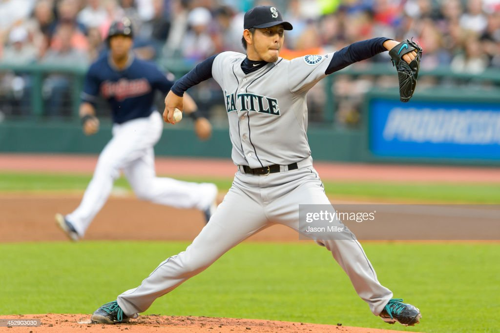 Starter Hisashi Iwakuma of the Seattle Mariners pitches as Michael Brantley of the Cleveland Indians leads off first base after drawing a walk during...
