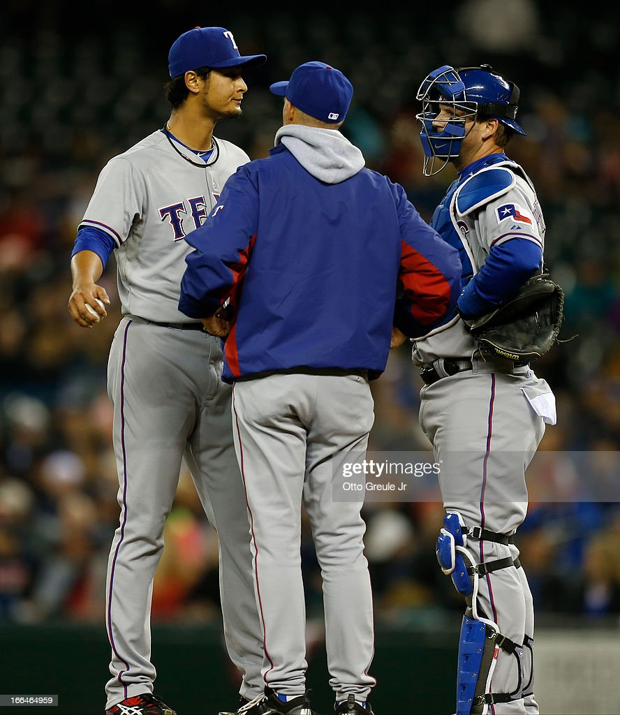 Starter <a gi-track='captionPersonalityLinkClicked' href=/galleries/search?phrase=Yu+Darvish&family=editorial&specificpeople=4018539 ng-click='$event.stopPropagation()'>Yu Darvish</a> #11 of the Texas Rangers gets a visit from pitching coach <a gi-track='captionPersonalityLinkClicked' href=/galleries/search?phrase=Mike+Maddux&family=editorial&specificpeople=556746 ng-click='$event.stopPropagation()'>Mike Maddux</a> #31 after yielding a walk to Kendrys Morales of the Seattle Mariners in the third inning at Safeco Field on April 12, 2013 in Seattle, Washington. Catcher A.J. Pierzynski #12 looks on.