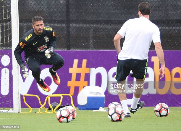 Starting goal keeper Alisson works with coach Rogerio Ceni during their training session at the University of Central Florida in Orlando on June 6...