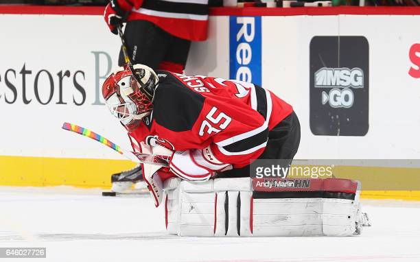 Starting goaltender Cory Schneider of the New Jersey Devils stretches during pregame warmups holding a rainbow stick in recognition of pride night...