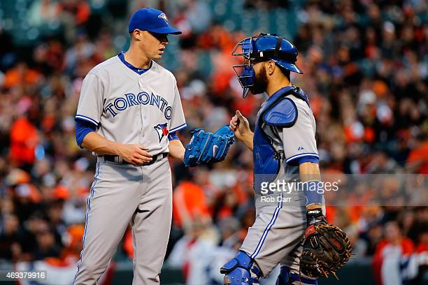 Starting pitcher Aaron Sanchez of the Toronto Blue Jays talks with catcher Russell Martin during the first inning against the Baltimore Orioles at...