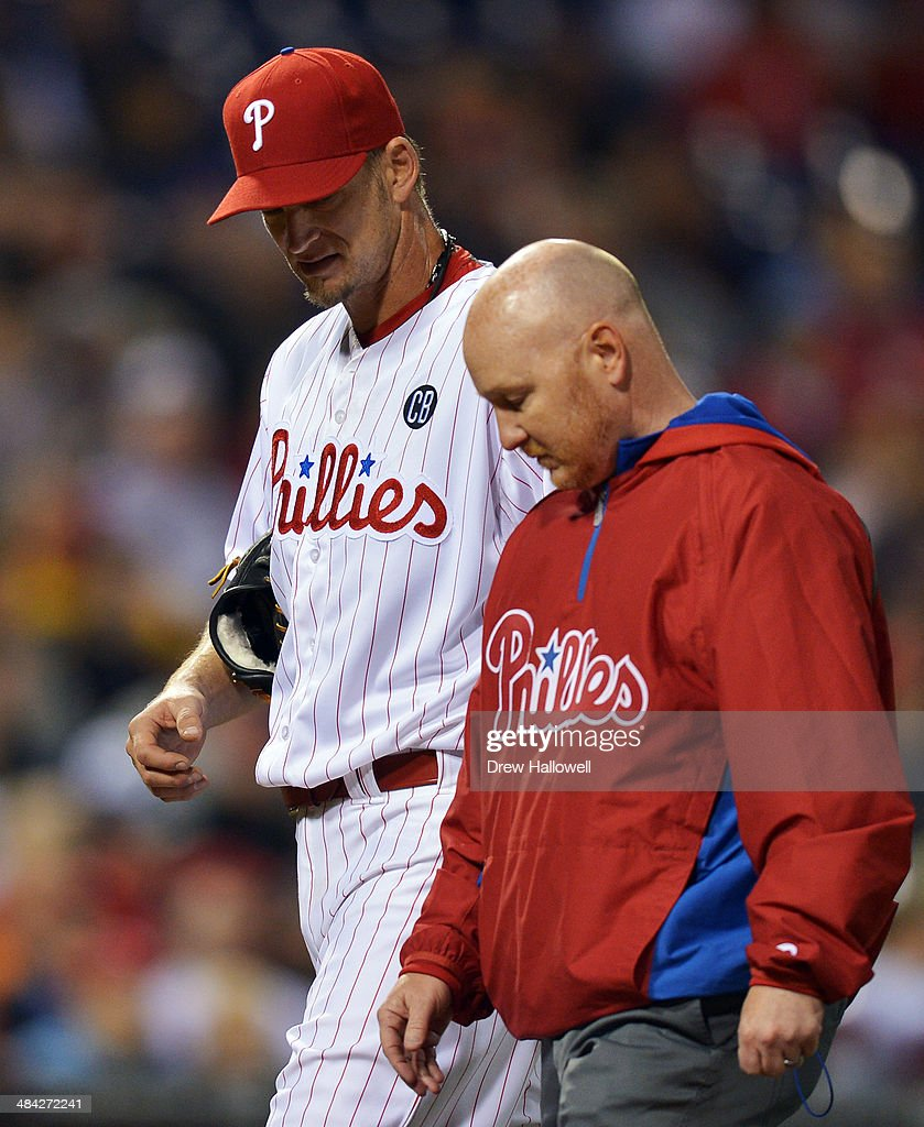 Starting pitcher A.J. Burnett #34 of the Philadelphia Phillies leaves the game with the trainer in the fifth inning against the Miami Marlins at Citizens Bank Park on April 11, 2014 in Philadelphia, Pennsylvania. The Phillies won 6-3.
