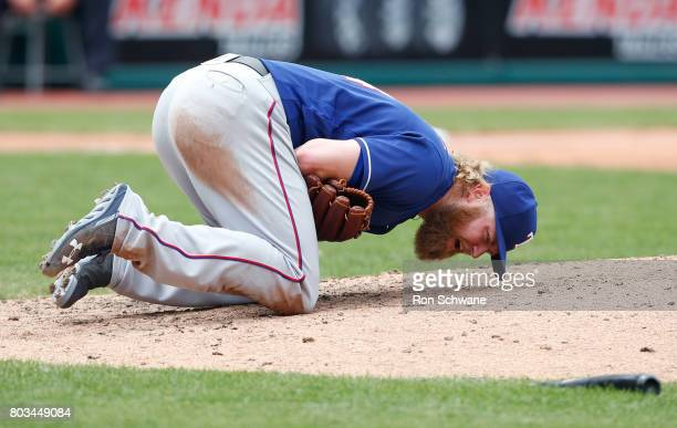 Starting pitcher Andrew Cashner of the Texas Rangers falls to the ground after being hit by a broken bat from Edwin Encarnacion of the Cleveland...