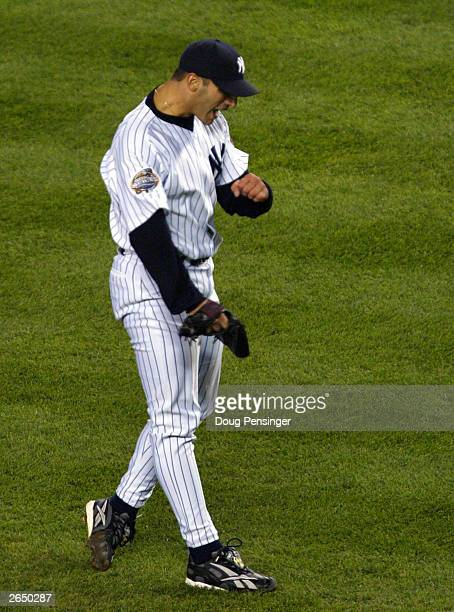Starting pitcher Andy Pettitte of the New York Yankees celebrates Derek Jeter throwing to ground out Mike Lowell of the Florida at first on a force...