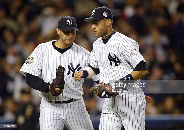 Starting pitcher Andy Pettitte of the New York Yankees congratulates teammate Derek Jeter after throwing out Mike Lowell of the Florida Marlins in...