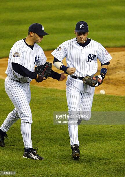 Starting pitcher Andy Pettitte of the New York Yankees congratulates teammate Derek Jeter after throwing out Mike Lowell of the Florida Marlins at...