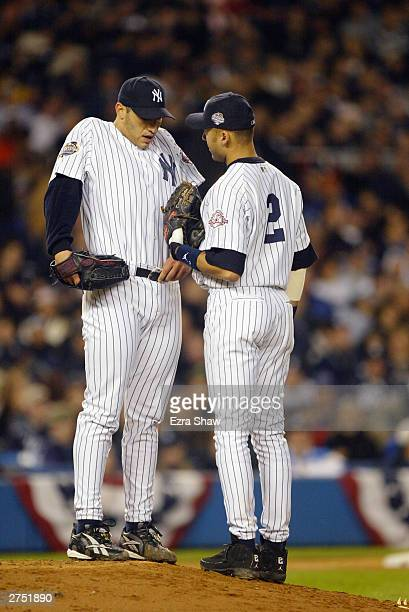 Starting pitcher Andy Pettitte talks with teammate Derek Jeter of the New York Yankees on the mound during game six of the Major League Baseball...