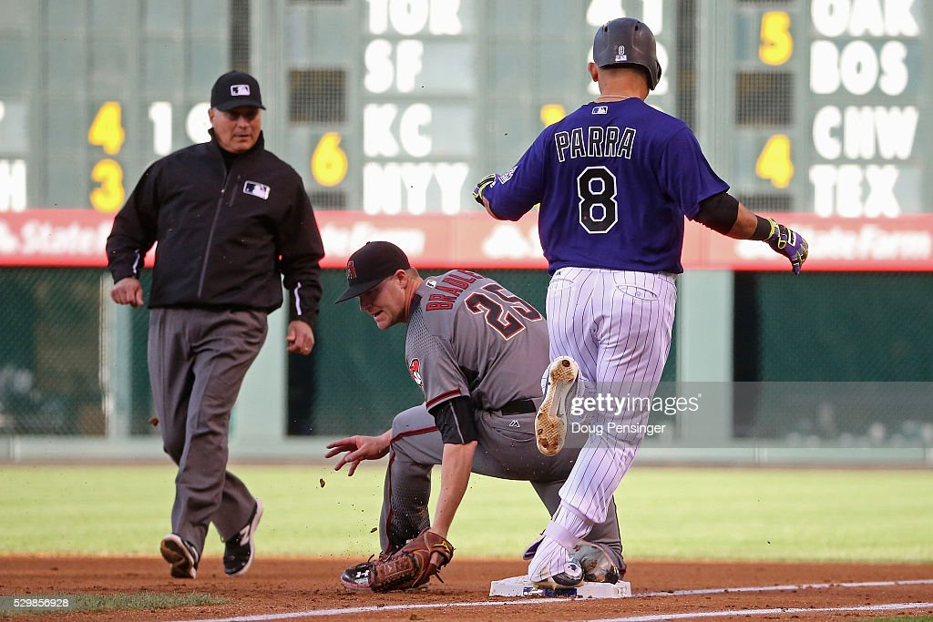 Starting pitcher Archie Bradley #25 of the Arizona Diamondbacks gets the put out on Gerardo Parra #8 of the Colorado Rockies at first base as he gounds out and umpire John Hirschbeck makes the call in the first inning at Coors Field on May 09, 2016 in Denver, Colorado.