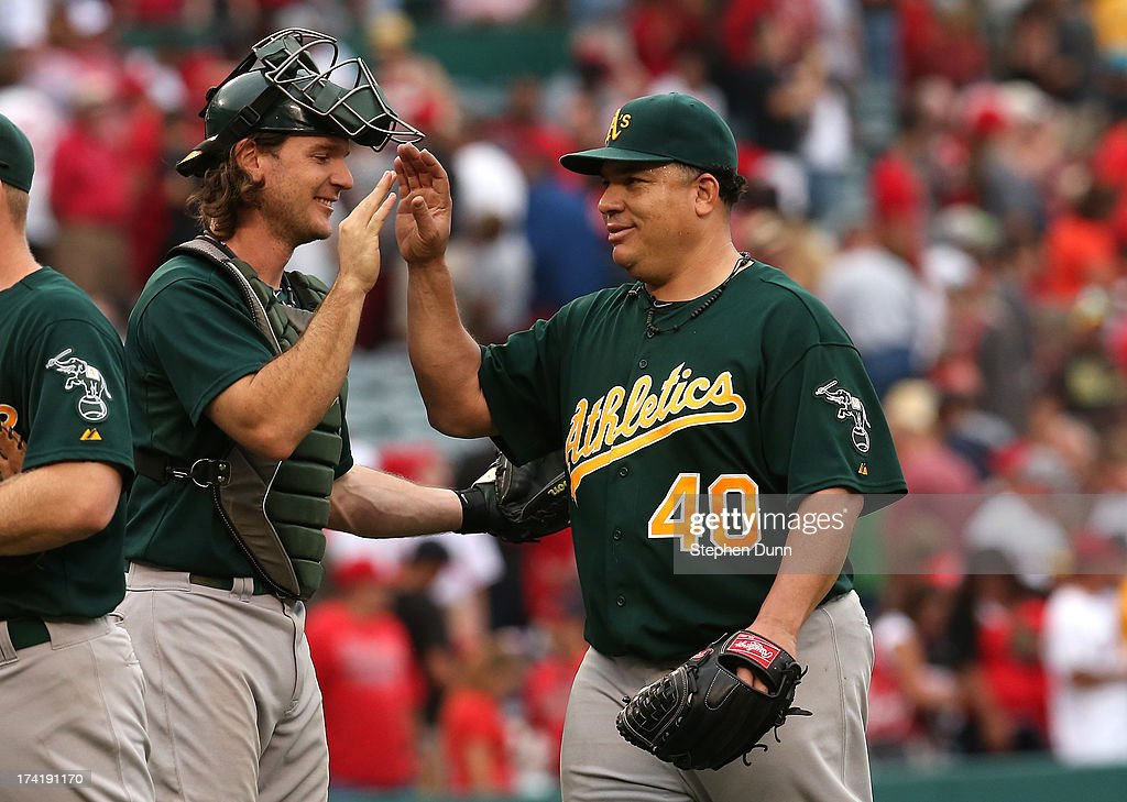 Starting pitcher <a gi-track='captionPersonalityLinkClicked' href=/galleries/search?phrase=Bartolo+Colon&family=editorial&specificpeople=175812 ng-click='$event.stopPropagation()'>Bartolo Colon</a> #40 and catcher <a gi-track='captionPersonalityLinkClicked' href=/galleries/search?phrase=John+Jaso&family=editorial&specificpeople=4951282 ng-click='$event.stopPropagation()'>John Jaso</a> #5 of the Oakland Athletics celebrate after the final out of Colon's complete game shutout against the Los Angeles Angels of Anaheim at Angel Stadium of Anaheim on July 21, 2013 in Anaheim, California. Oakland won 6-0.