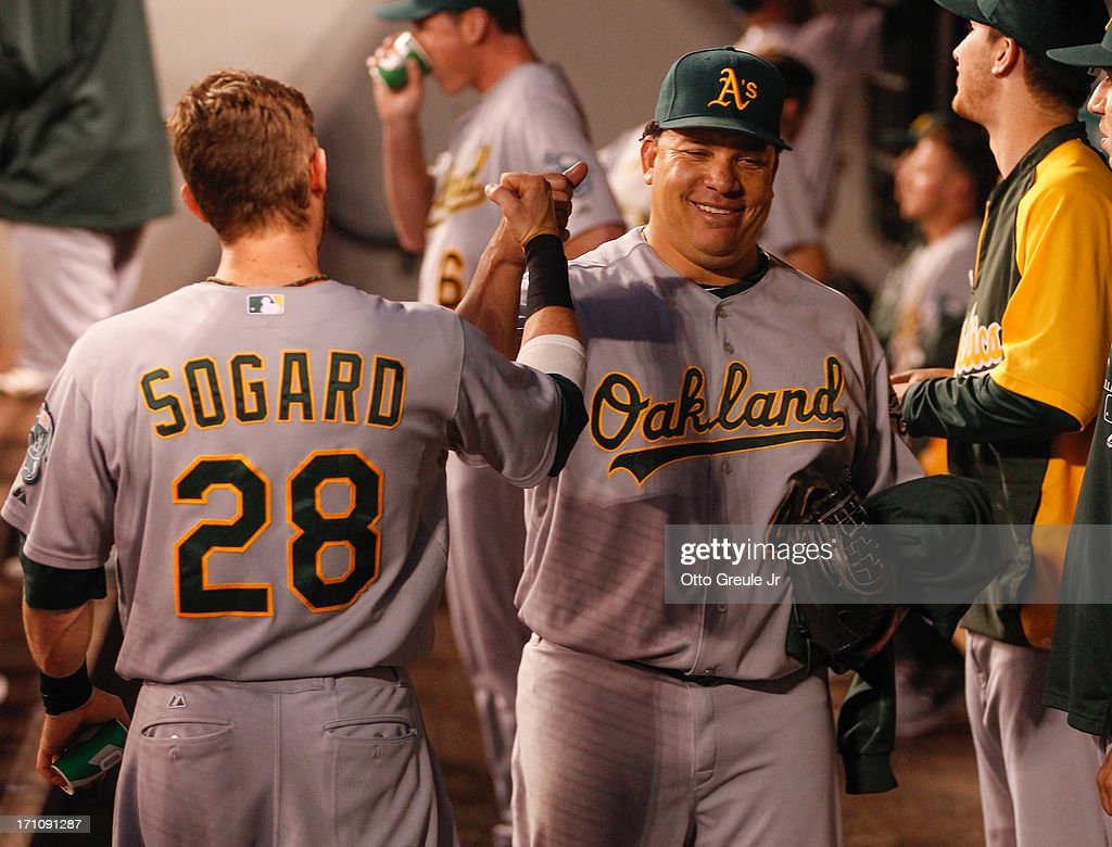 Starting pitcher <a gi-track='captionPersonalityLinkClicked' href=/galleries/search?phrase=Bartolo+Colon&family=editorial&specificpeople=175812 ng-click='$event.stopPropagation()'>Bartolo Colon</a> #40 of the Oakland Athletics is congratulated by <a gi-track='captionPersonalityLinkClicked' href=/galleries/search?phrase=Eric+Sogard&family=editorial&specificpeople=6796459 ng-click='$event.stopPropagation()'>Eric Sogard</a> #28 after retiring the Seattle Mariners in the eighth inning at Safeco Field on June 21, 2013 in Seattle, Washington.