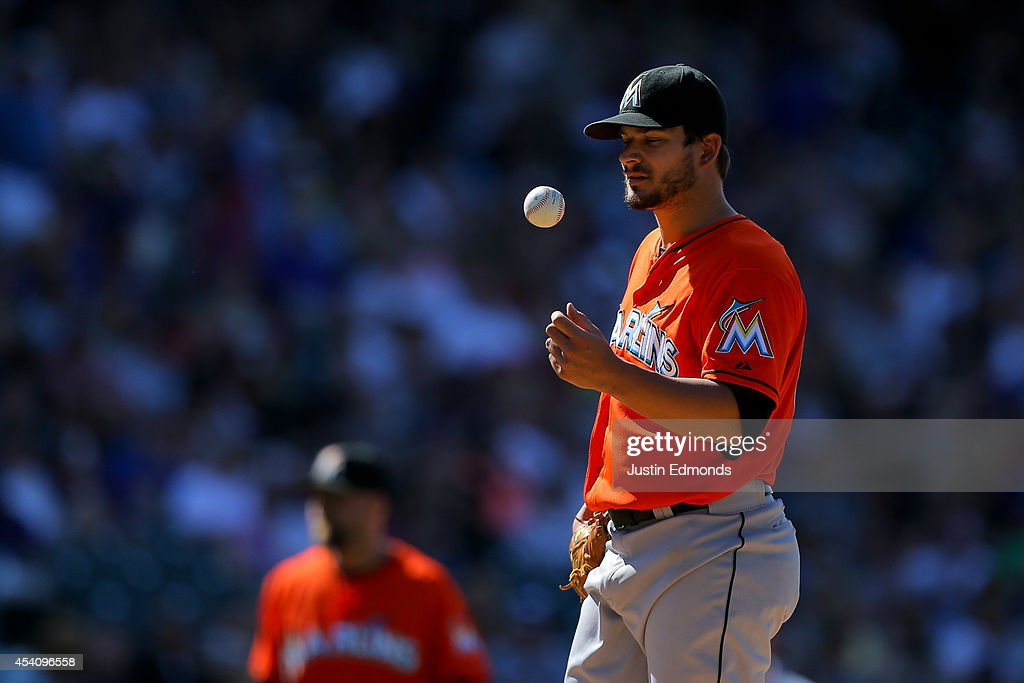 Starting pitcher Brad Hand of the Miami Marlins tosses the ball just prior to being removed from the game during the fifth inning against the...