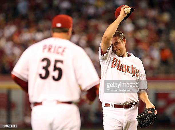 Starting pitcher Brandon Webb of the Arizona Diamondbacks wipes up his face as pitching coach Bryan Price approaches the mound during the MLB...