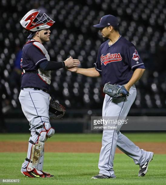 Starting pitcher Carlos Carrasco of the Cleveland Indians celebrates with Roberto Perez after a complete game win against the Chicago White Sox at...
