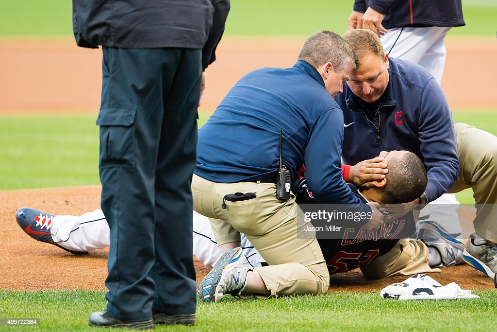 Starting pitcher Carlos Carrasco #59 of the Cleveland Indians is helped up by team trainers after being hit in the face by a line drive off the bat of Melky Cabrera of the Chicago White Sox during the first inning at Progressive Field on April 14, 2015 in Cleveland, Ohio.