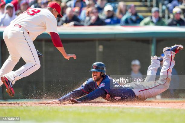 Starting pitcher Carlos Carrasco of the Cleveland Indians jumps over Trevor Plouffe of the Minnesota Twins as Plouffe scores from third on a passed...