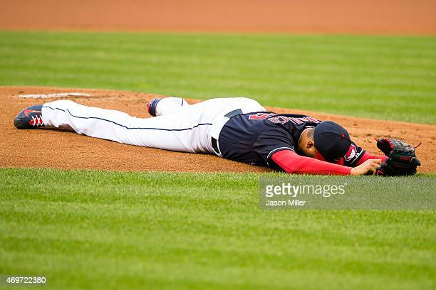 Starting pitcher Carlos Carrasco of the Cleveland Indians lies on the ground after being hit in the face by a line drive off the bat of Melky Cabrera...