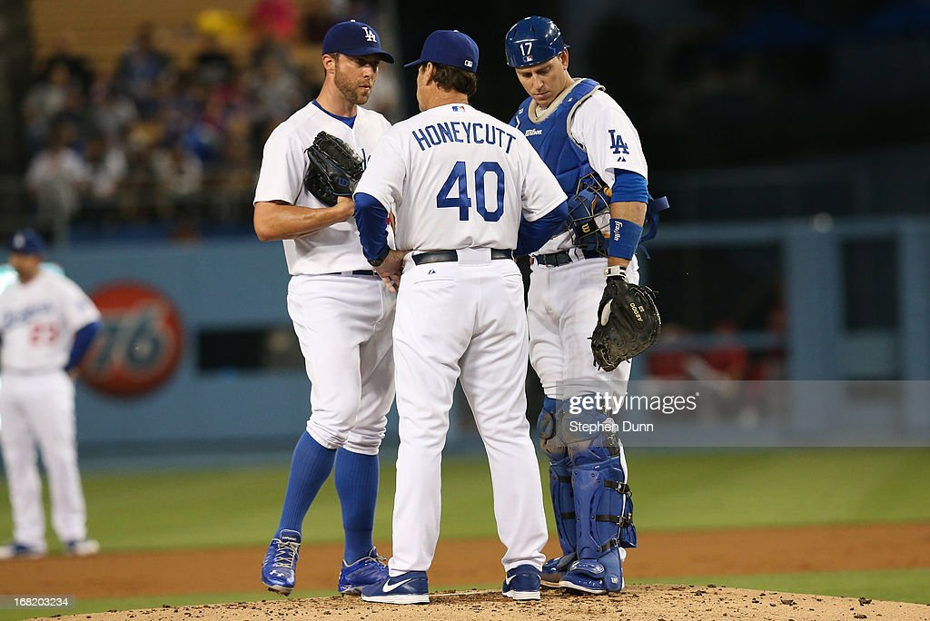 Starting pitcher <a gi-track='captionPersonalityLinkClicked' href=/galleries/search?phrase=Chris+Capuano&family=editorial&specificpeople=228059 ng-click='$event.stopPropagation()'>Chris Capuano</a> #35 of the Los Angeles Dodgers meets with pitching coach Rick Honeycutt #40 and catcher A.J. Ellis #17 in the second inning against the Arizona Diamondbacks at Dodger Stadium on May 6, 2013 in Los Angeles, California.