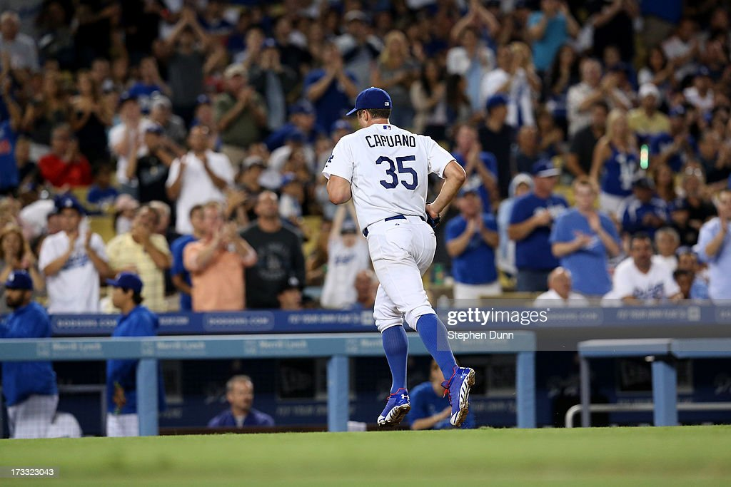 Starting pitcher <a gi-track='captionPersonalityLinkClicked' href=/galleries/search?phrase=Chris+Capuano&family=editorial&specificpeople=228059 ng-click='$event.stopPropagation()'>Chris Capuano</a> #35 of the Los Angeles Dodgers runs off the field to cheers as he is relieved in th seventh inning after pitching 6 1/3 scoreless innings against the Colorado Rockies at Dodger Stadium on July 11, 2013 in Los Angeles, California.