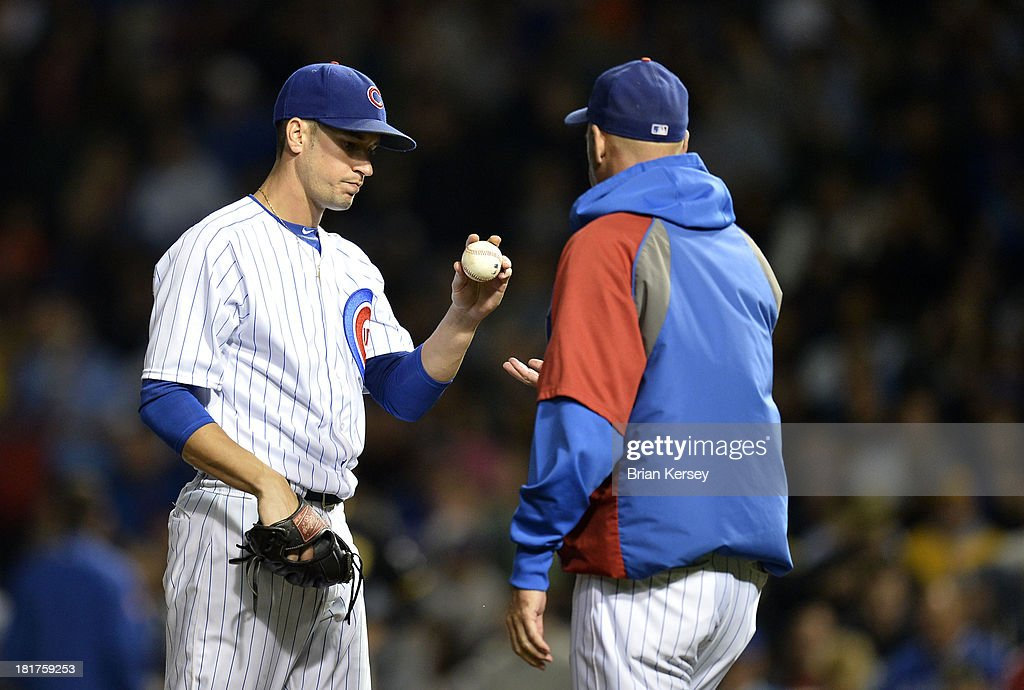 Starting pitcher Chris Rusin #18 of the Chicago Cubs (L) hands the ball to manager Dale Sveum #4 as he is taken out of the game during the third inning against the Pittsburgh Pirates at Wrigley Field on September 24, 2013 in Chicago, Illinois.