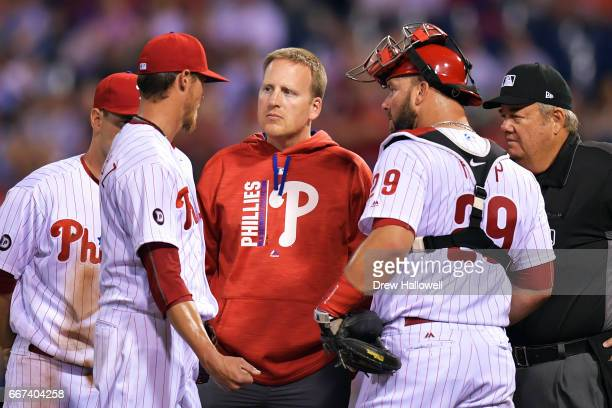 Starting pitcher Clay Buchholz of the Philadelphia Phillies talks with team trainer Shawn Fcasni before leaving the game against the New York Mets at...