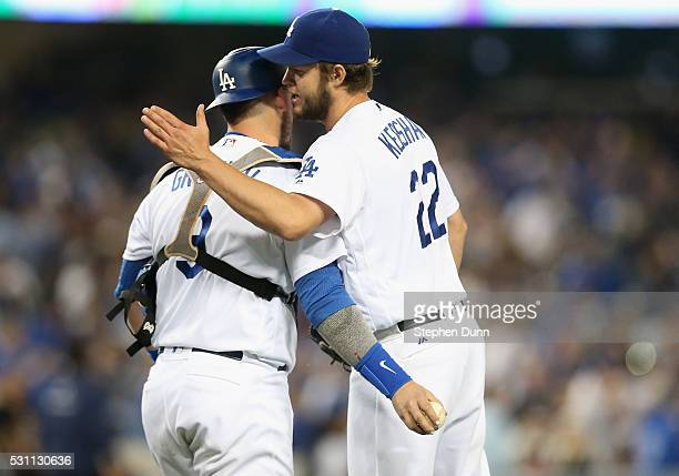 Starting pitcher Clayton Kershaw and catcher Yasmani Grandal of the Los Angeles Dodgers celebrate after the final out of the game against the New...