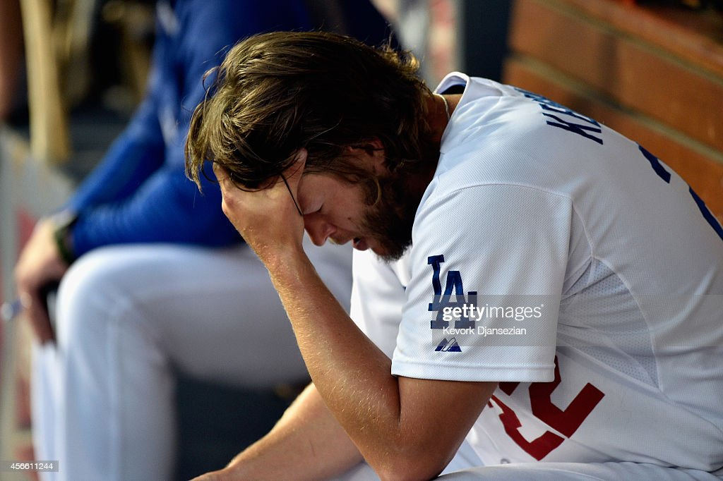 Starting pitcher Clayton Kershaw of the Los Angeles Dodgers reacts in the dugout during the seventh inning of Game One of the National League...