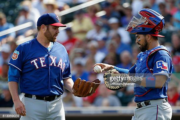 Starting pitcher Colby Lewis of the Texas Rangers takes a ball from catcher Robinson Chirinos during the first inning of the cactus leauge spring...