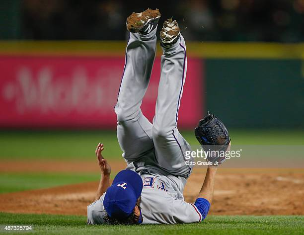 Starting pitcher Cole Hamels of the Texas Rangers tumbles off the mound after being hit with a comebacker off the bat of Jesus Sucre of the Seattle...