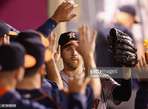 Starting pitcher Colin McHugh of the Houston Astros is greeted by teammates as he returns to the dugout after being relieved in the eighth inning of...