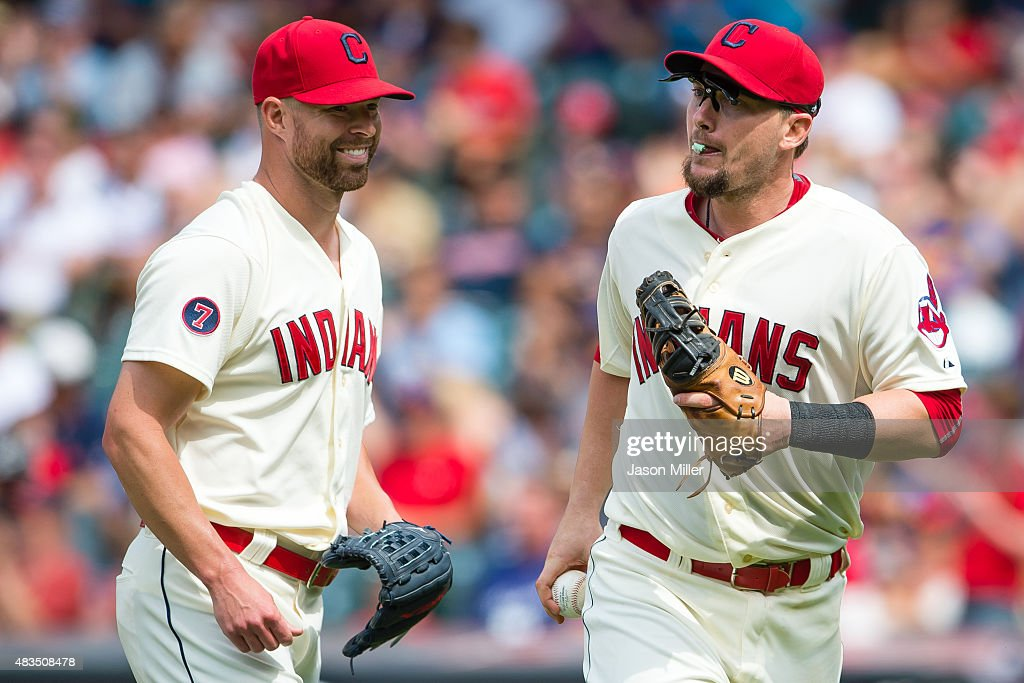 Starting pitcher Corey Kluber jokes with first baseman Chris Johnson of the Cleveland Indians after the eighth inning against the Minnesota Twins at...