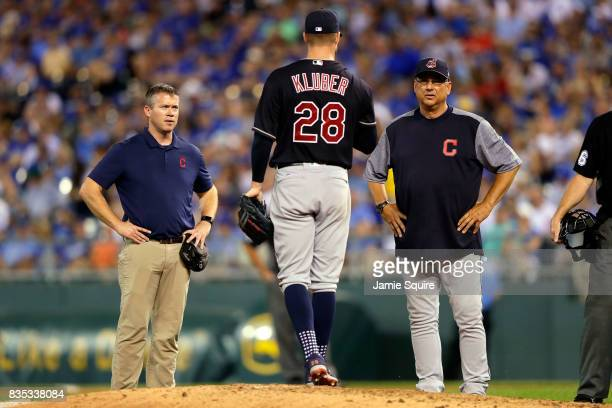 Starting pitcher Corey Kluber of the Cleveland Indians is tended to by manager Terry Francona and a trainer during the 6th inning of the game against...