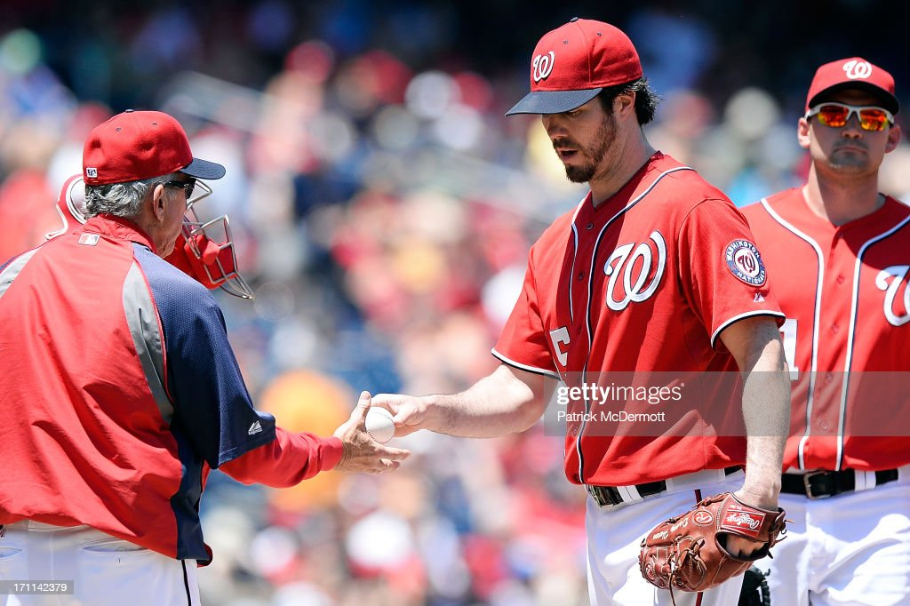 Starting pitcher <a gi-track='captionPersonalityLinkClicked' href=/galleries/search?phrase=Dan+Haren&family=editorial&specificpeople=228587 ng-click='$event.stopPropagation()'>Dan Haren</a> #15 of the Washington Nationals hands the ball to manager <a gi-track='captionPersonalityLinkClicked' href=/galleries/search?phrase=Davey+Johnson+-+Baseball+Manager&family=editorial&specificpeople=93273 ng-click='$event.stopPropagation()'>Davey Johnson</a> #5 as he is pulled in the fourth inning during a game against the Colorado Rockies at Nationals Park on June 22, 2013 in Washington, DC.