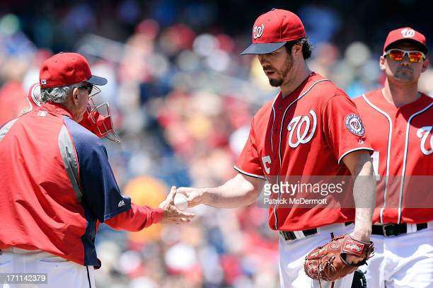 Starting pitcher Dan Haren of the Washington Nationals hands the ball to manager Davey Johnson as he is pulled in the fourth inning during a game...