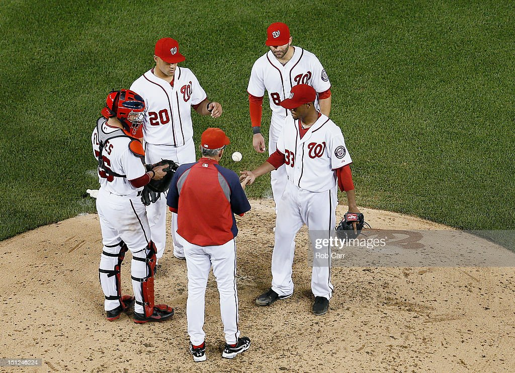 Starting pitcher Edwin Jackson of the Washington Nationals flips the ball to manager Davey Johnson after being pulled during the sixth inning against...