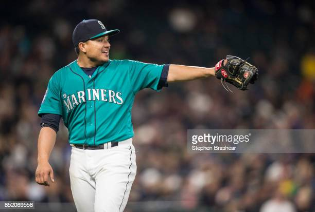 Starting pitcher Erasmo Ramirez of the Seattle Mariners gestures to first baseman Yonder Alonso of the Seattle Mariners after pitching in the fifth...