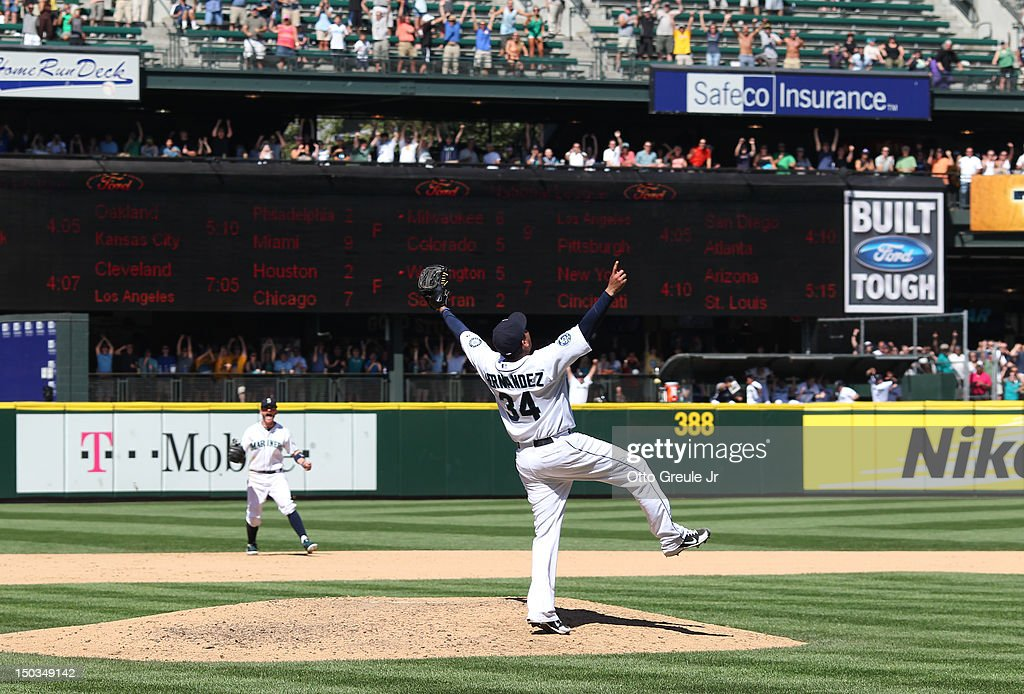 Starting pitcher <a gi-track='captionPersonalityLinkClicked' href=/galleries/search?phrase=Felix+Hernandez&family=editorial&specificpeople=550749 ng-click='$event.stopPropagation()'>Felix Hernandez</a> #34 of the Seattle Mariners and shortstop Brendan Ryan #26 celebrate after Hernandez threw the 23rd perfect game in Major League Baseball history to defeat the Tampa Bay Rays 1-0 at Safeco Field on August 15, 2012 in Seattle, Washington.