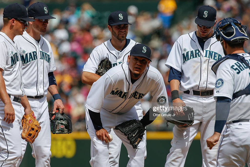 Starting pitcher <a gi-track='captionPersonalityLinkClicked' href=/galleries/search?phrase=Felix+Hernandez&family=editorial&specificpeople=550749 ng-click='$event.stopPropagation()'>Felix Hernandez</a> #34 of the Seattle Mariners is surrounded by teammates as he pauses on the mound after striking out Chris Stewart of the New York Yankees in the seventh inning at Safeco Field on June 9, 2013 in Seattle, Washington. Hernandez remained in the game after a visit from the trainer.