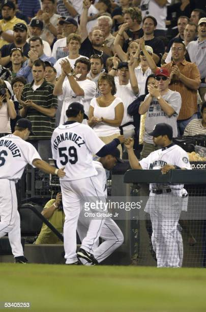 Starting Pitcher Felix Hernandez of the Seattle Mariners is congratulated by teammates he walks to the dugout during the game against the Minnesota...