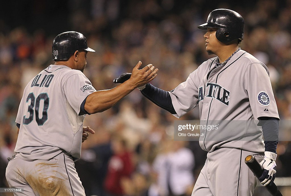 Starting pitcher Felix Hernandez #34 of the Seattle Mariners congratulates Miguel Olivo #30 after he scored in the seventh inning against the Florida Marlins at Safeco Field on June 24, 2011 in Seattle, Washington.