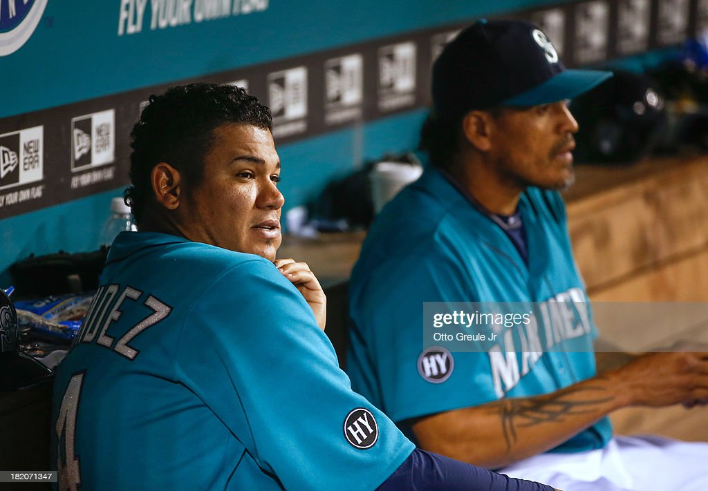 Starting pitcher Felix Hernandez #34 (L) of the Seattle Mariners sits on the bench with teammate Henry Blanco #33 at the start of the seventh inning against the Oakland Athletics at Safeco Field on September 27, 2013 in Seattle, Washington. Hernandez was removed after throwing six innings.