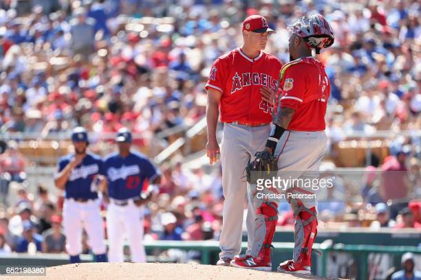 Starting pitcher Garrett Richards of the Los Angeles Angels talks with catcher Martin Maldonado on the mound during the third inning of the MLB...