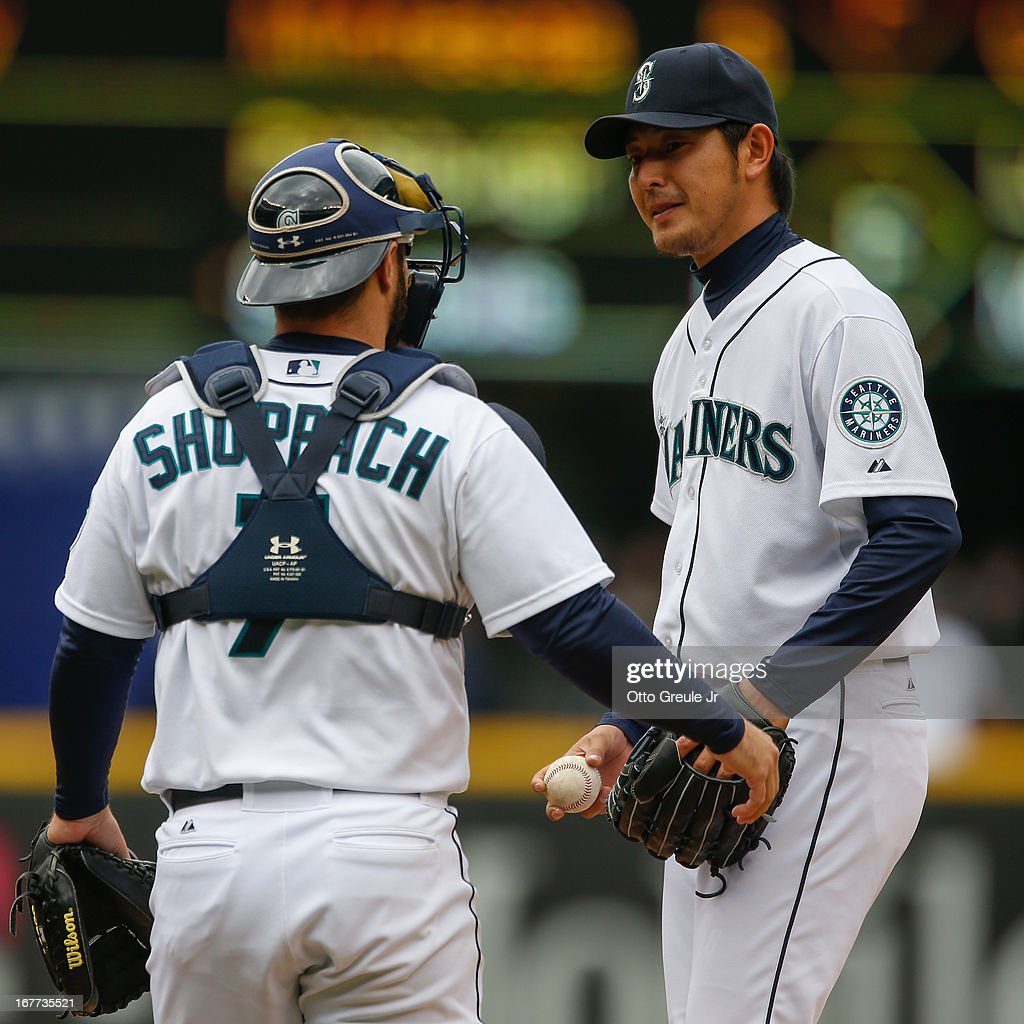 Starting pitcher Hisashi Iwakuma #18 of the Seattle Mariners gets a visit from catcher Kelly Shoppach #7 against the Los Angeles Angels of Anaheim at Safeco Field on April 28, 2013 in Seattle, Washington.
