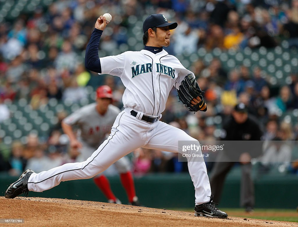 Starting pitcher <a gi-track='captionPersonalityLinkClicked' href=/galleries/search?phrase=Hisashi+Iwakuma&family=editorial&specificpeople=5723798 ng-click='$event.stopPropagation()'>Hisashi Iwakuma</a> #18 of the Seattle Mariners pitches in the first inning with Peter Bourjos #25 of the Los Angeles Angels of Anaheim on first base at Safeco Field on April 28, 2013 in Seattle, Washington. The Mariners defeated the Angels 2-1.