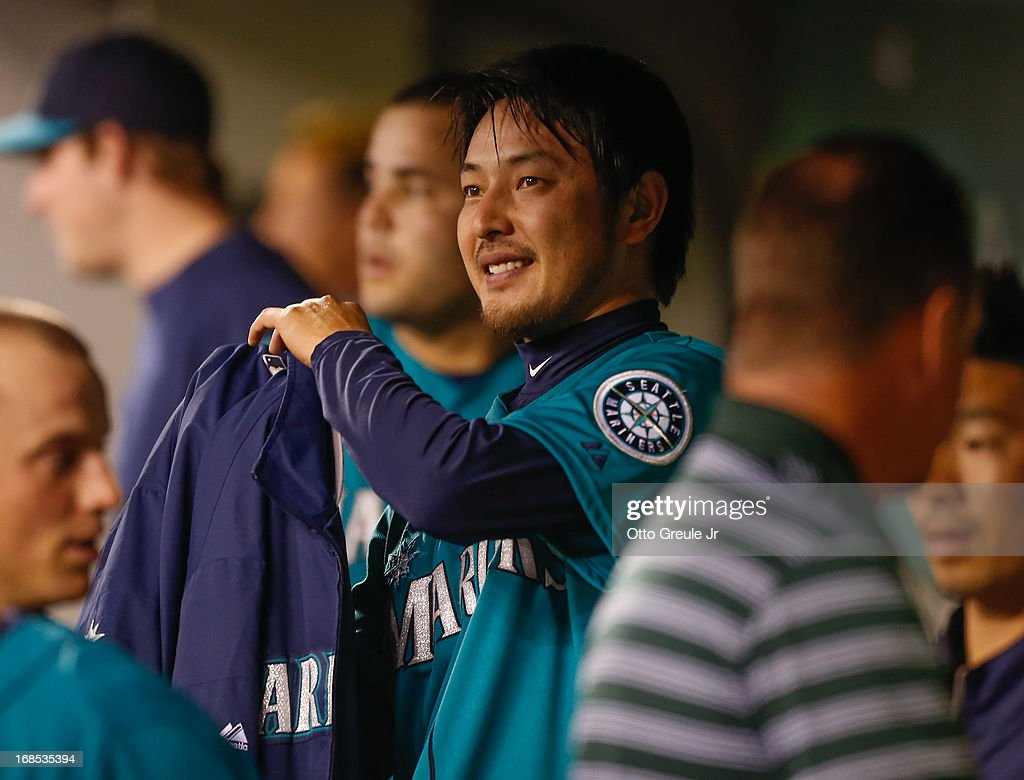 Starting pitcher <a gi-track='captionPersonalityLinkClicked' href=/galleries/search?phrase=Hisashi+Iwakuma&family=editorial&specificpeople=5723798 ng-click='$event.stopPropagation()'>Hisashi Iwakuma</a> #18 of the Seattle Mariners smiles as he puts his jacket on in the dugout during the game against the Oakland Athletics at Safeco Field on May 10, 2013 in Seattle, Washington.