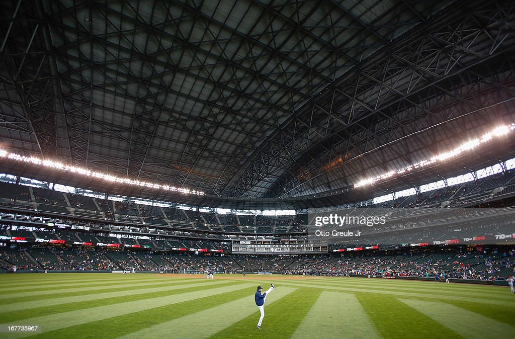 Starting pitcher Hisashi Iwakuma #18 of the Seattle Mariners warms up in the outfield prior to the game against the Los Angeles Angels of Anaheim at Safeco Field on April 28, 2013 in Seattle, Washington. The Mariners defeated the Angels 2-1.