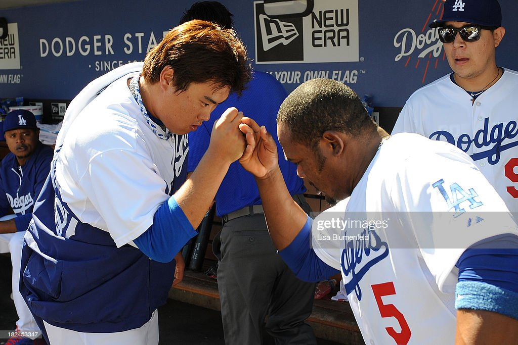 Starting pitcher Hyun-Jin Ryu #99 and teammate <a gi-track='captionPersonalityLinkClicked' href=/galleries/search?phrase=Juan+Uribe&family=editorial&specificpeople=209187 ng-click='$event.stopPropagation()'>Juan Uribe</a> #5 of the Los Angeles Dodgers prepare for the game against the Colorado Rockies at Dodger Stadium on September 29, 2013 in Los Angeles, California.
