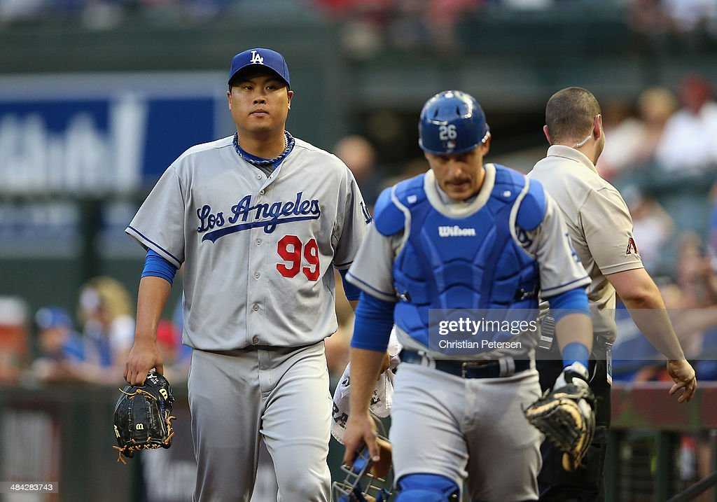 Starting pitcher Hyun-Jin Ryu #99 of the Los Angeles Dodgers walks to the dugout with catcher Tim Federowicz #26 before the MLB game against the Arizona Diamondbacks at Chase Field on April 11, 2014 in Phoenix, Arizona. The Dodgers defeated the Diamondbacks 6-0.