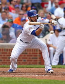 Starting pitcher Jake Arrieta of the Chicago Cubs bunts in a run in the 3rd inning against the Atlanta Braves at Wrigley Field on July 11 2014 in...