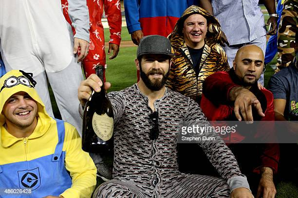 Starting pitcher Jake Arrieta of the Chicago Cubs holds up a bottle as he sits with teammates as they all wear pajamas as part of a theme trip after...